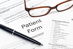 Patient medical forms with pen and glasses